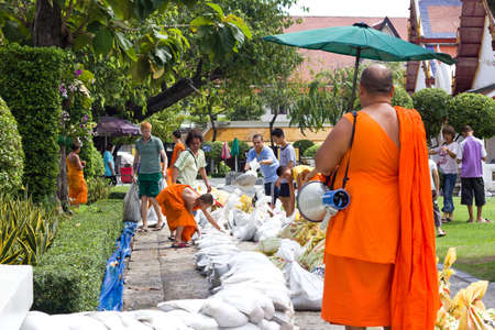 BANGKOK THAILAND - OCTOBER 29 : People and monk bringing sandbags to prevent flooding in wat arun  on October 29, 2011 in Bangkok, Thailand. Stock Photo - 11044636