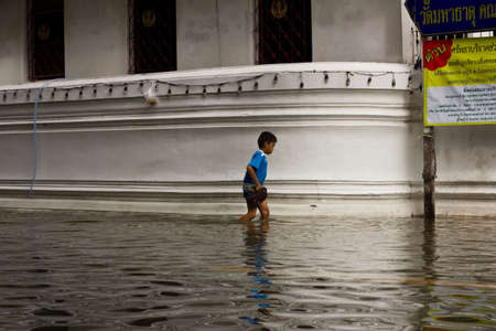 BANGKOK THAILAND - OCTOBER 29 : An unidentified boy is wallking through a flooded street on October 29, 2011 in Bangkok, Thailand.