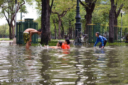BANGKOK, THAILAND - OCTOBER 30 : People playing water on the street during flood on October 30,2011  Bangkok, Thailand. Stock Photo - 11063810