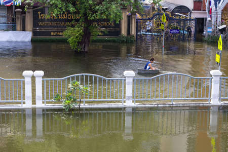 inundated: BANGKOK, THAILAND - OCTOBER 30 : An unidentified man uses a enameled bowl as a boat during the worst flooding in decades on October 30,2011  Bangkok, Thailand. Editorial