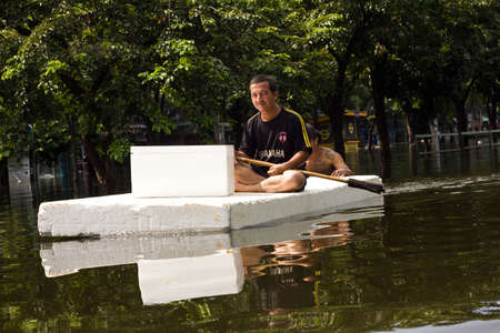 worst: BANGKOK, THAILAND - OCTOBER 30 : An unidentified man uses a foam board. as a boat  during the worst flooding in decades on October 30,2011  Bangkok, Thailand.