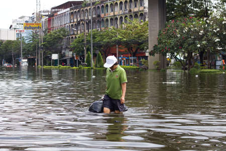 BANGKOK, THAILAND - OCTOBER 30 :  An unidentified woman wading through the flood after the monsoon rain on October 30,2011  Bangkok, Thailand. Editorial
