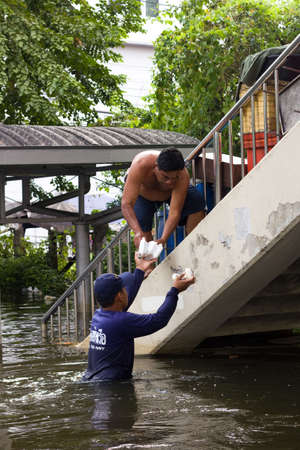 inundated: BANGKOK, THAILAND - OCTOBER 30 : The Royal Thai Navy bringing food for people during the monsoon season on October 30,2011  Bangkok, Thailand. A man living on the bridge Editorial