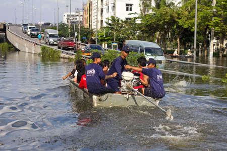 inundated: BANGKOK, THAILAND - OCTOBER 30 : Rescue teams helping people to get home during the worst flooding in decades on October 30,2011  Bangkok, Thailand.