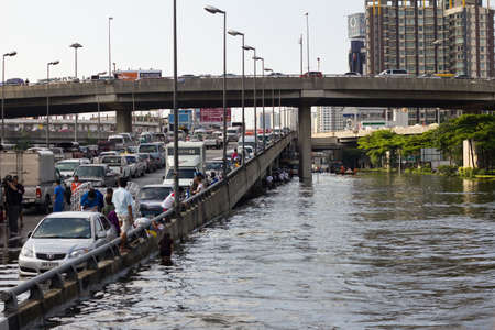 BANGKOK, THAILAND - OCTOBER 30 : Heavy flooding from monsoon rain in Ayutthaya and north Thailand arriving in Bangkok on October 30,2011  Bangkok, Thailand. People Bringing car park on the brigde Stock Photo - 11063856