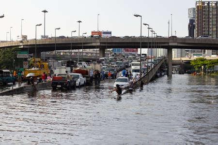 BANGKOK, THAILAND - OCTOBER 30 : Heavy flooding from monsoon rain in Ayutthaya and north Thailand arriving in Bangkok on October 30,2011  Bangkok, Thailand. People Bringing car park on the brigde
