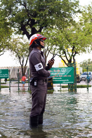 BANGKOK, THAILAND - OCTOBER 30 : An unidentified Thai policeman working on the flooded streets on October 30,2011  Bangkok, Thailand.