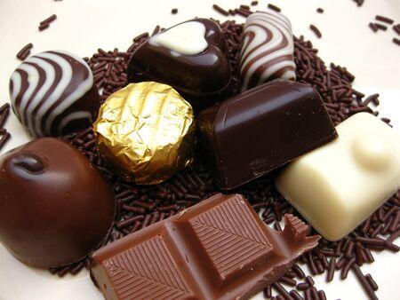 Belgium chocolate candies and milk chocolate on chocolate sprinkles photo