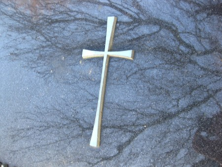 mortal: cross on gravestone with reflection of trees Stock Photo