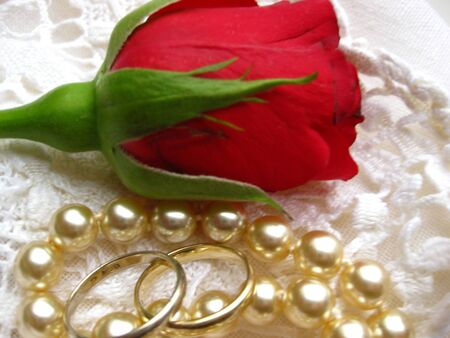 wedding bands, pearls and a rose on lace Stock Photo - 4217241