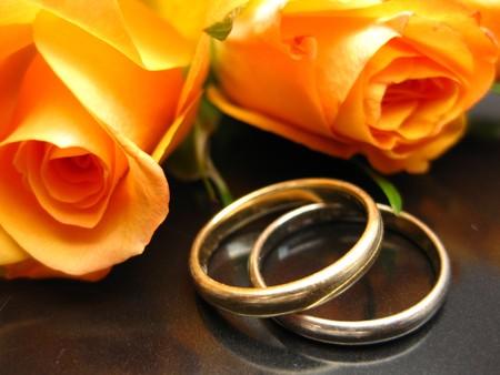 Weddingbands and orange roses photo