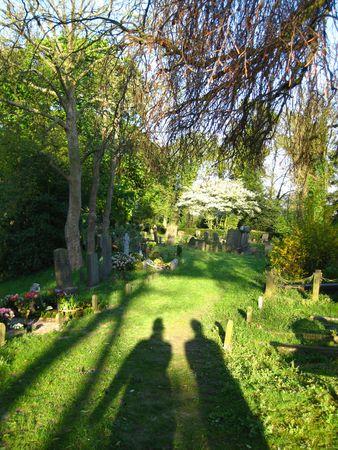 crematorium: silhouettes of people walking on graveyard Stock Photo