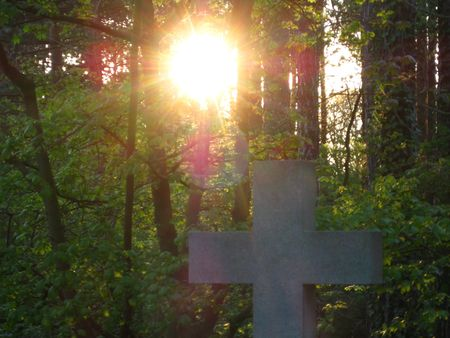 simple cross on a grave in the sunset
