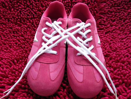 A pair of pink sneakers on a pink carpet photo