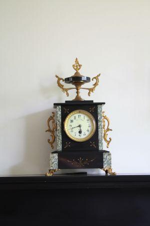 Vintage marble clock on black marble fireplace photo