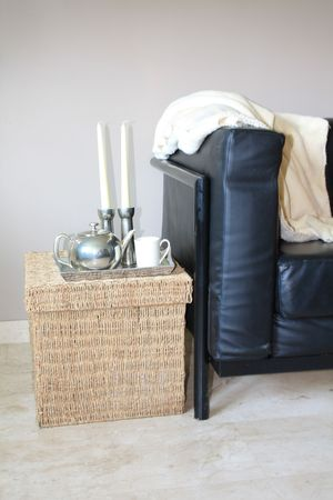 Interior design: Black leather sofa and wicker footstool, serving tray with silver accessoiries Stock Photo - 5386888