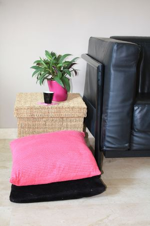 footstool: Interior design: black leather sofa, wicker footstool and pink pillows Stock Photo