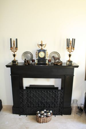 Black marble fireplace with antique clock and matching candleholders Stock Photo