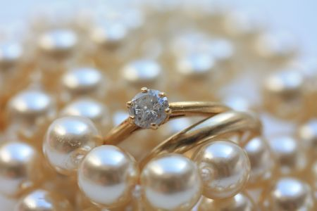 Wedding band and engagement ring on pearls Stock Photo - 5380287