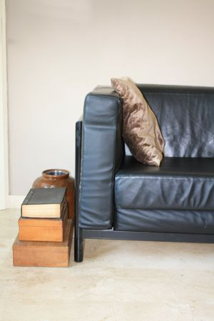 Interior design: Black leather sofa, vintage wooden boxes and olive pot photo