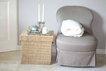 footstool: Interior design: Classic Biedermeier chair and wicker footstool, serving tray with silver accessoiries