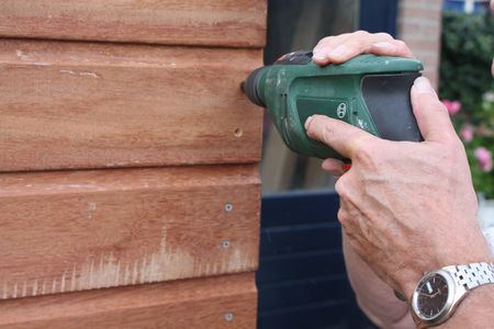 electric saw: Man working with a power drill on a wooden construction Stock Photo