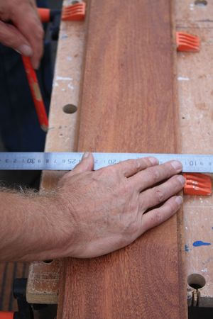 A Carpenter Getting Ready For Work, measuring wood Stock Photo
