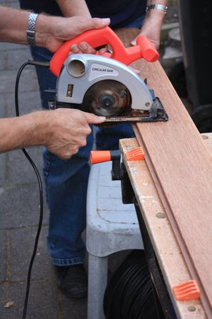 construction worker cutting wood with circular saw Stock Photo - 5568276