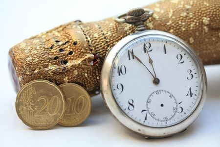 A champagne bottle, a vintage pocket watch and two euro coins. Perfect New Years greeting card photo