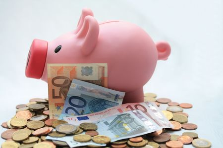 Piggy bank on a set of various euro coins and banknotes Stock Photo - 5627586