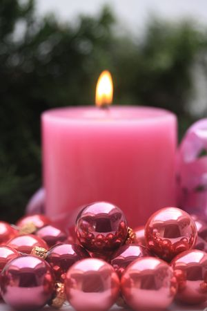 A pink candle and some small pink christmas balls photo