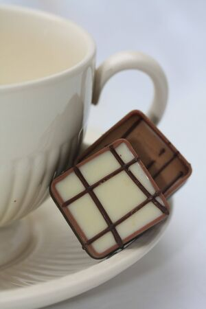 Two luxury chocolates on a tea cup saucer photo