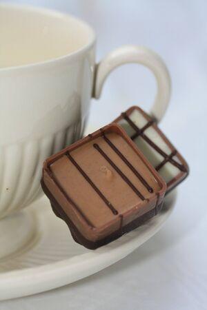 Two belgium chocolate pralines on a tea cup saucer photo