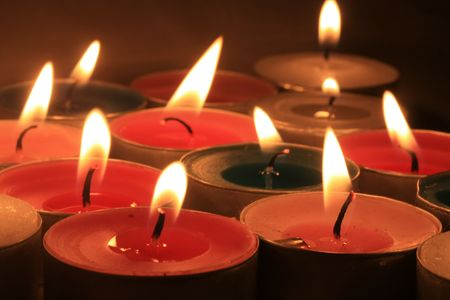 scented candle: A group of burning votive candles in different colors