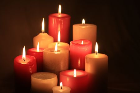 scented candle: A group of burning candles, different sizes in red and white