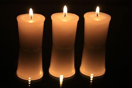 Gruppe von drei brennenden Votiv Lichter reflektiert in einem Spiegel Standard-Bild - 5841475