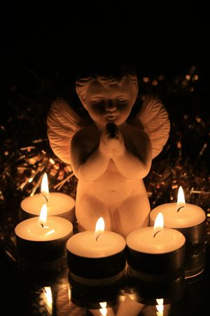 prayer candles: A white angel saying a prayer in candle light