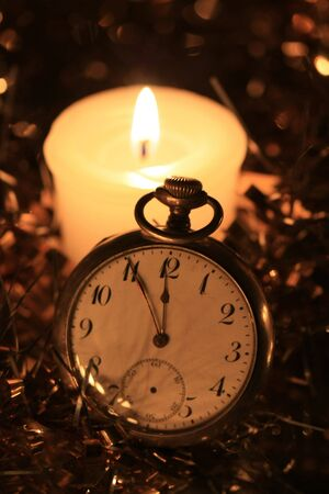 A vintage pocket watch in the candlelight, counting down for the new year Stock Photo - 5841486
