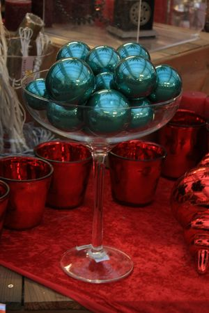 A glass bowl filled with green christmas ornaments photo
