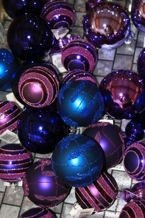 Collection of blue and purple christmas ornaments displayed in a shop photo