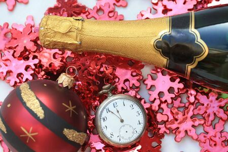 A bottle of champage with a pocket watch and red christmas decorations
