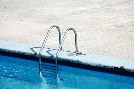 house float on water: A metal ladder on the side of a swimming pool