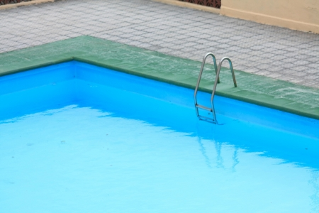 A ladder on the side of a swimming pool photo