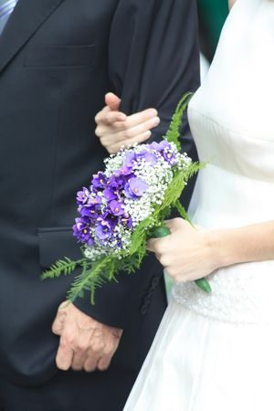 A bride walking to the church, holding her purple wedding bouquet Stock Photo - 6071885