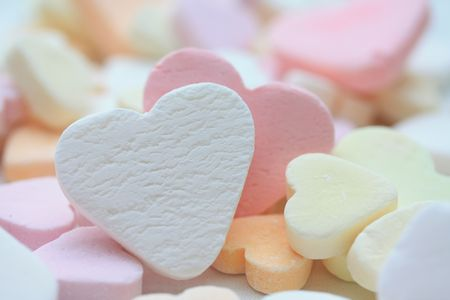 white fruit candy heart on a pile of candy hearts Stock Photo
