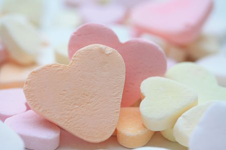 orange fruit candy heart on a pile of candy hearts photo