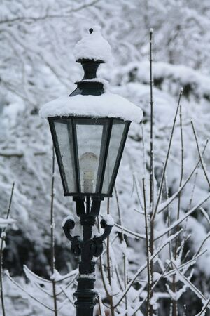 unlit: A vintage lantern covered in snow Stock Photo