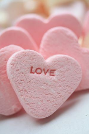 A pink valentine candy heart with the word love