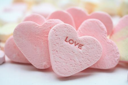 confession: A pink valentine candy heart with the word love
