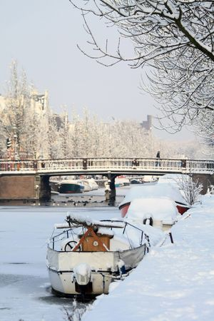 A frozen canal with snow coverd boats in Haarlem, Holland photo